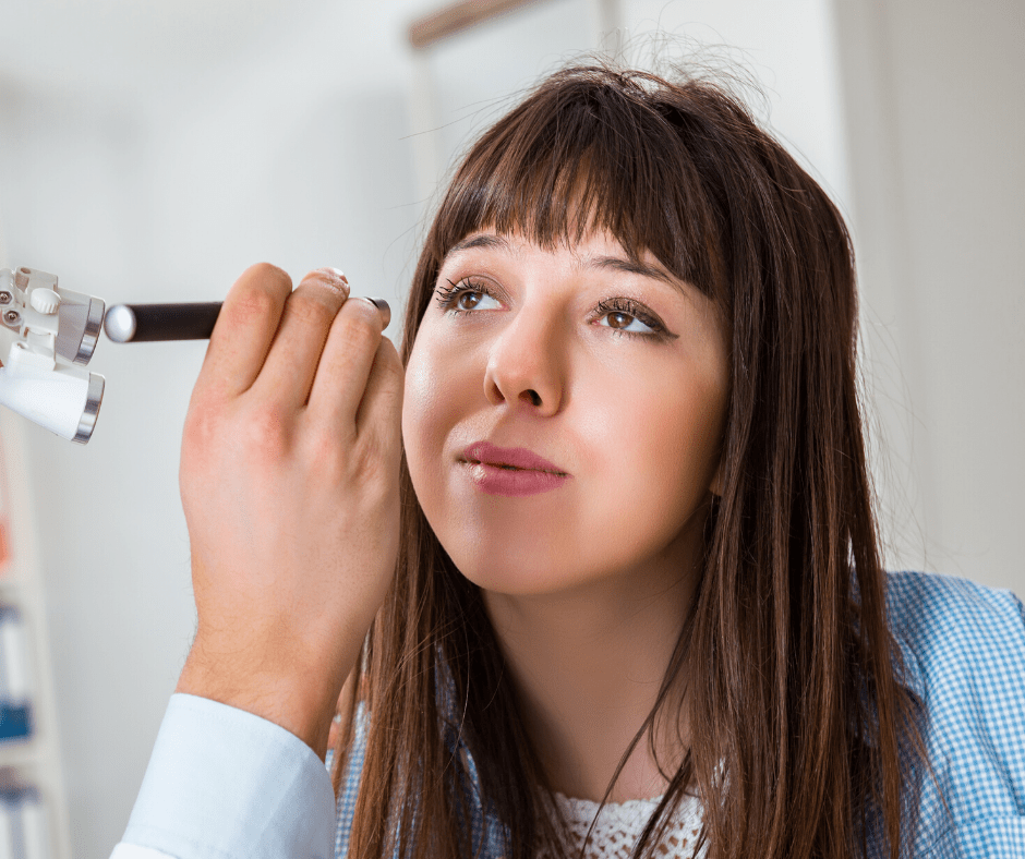 Light shining into womans eye by doctor